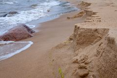 View of the sandy beach. The sandy beach, similar to the rocky coast, which is washed away by waves royalty free stock image
