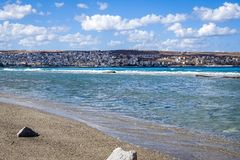View from the sandy Mediterranean beach to the other side of the coast. On the other side there is a large mountain with a small town on its foot; beautiful Royalty Free Stock Image