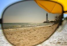 View of the sandy seashore through the sunglasses stock image
