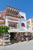 View in Sant Elm. SANT ELM, BALEARIC ISLANDS, SPAIN - JULY 10, 2016: Balcony flowers and souvenir shop with customer in Sant Elm on a sunny summer day on July 10 Stock Photos