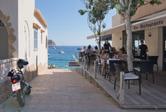 View in Sant Elm. SANT ELM, BALEARIC ISLANDS, SPAIN - JULY 10, 2016: Restaurant with ocean view with people and parked motorcycle in Sant Elm on a sunny summer Stock Photography