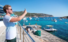View in Sant Elm. SANT ELM, BALEARIC ISLANDS, SPAIN - JULY 10, 2016: Young man taking photo with smartphone in Sant Elm on a sunny summer day on July 10, 2016 in Stock Image
