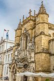 View of the Santa Cruz Monastery front facade, romanesque and gothic style, with tourists on street , a National Monument in royalty free stock image