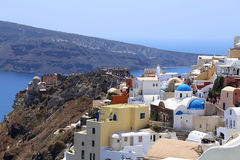 View on Santorini looking at colourful buildings dome churches with mountain and sea in the background. royalty free stock photography