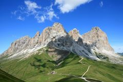 View of the Sassolungo Massif, Italian Dolomites. The village of Campitello is massively overlooked by the majestic Sassolungo and Col Rodella, where it is stock image