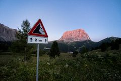 View of Sassolungo with a road sign in the forground royalty free stock images