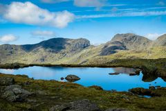 View of Scafell Pike from the South East with the mountain reflected in a nearby body of water under a cloudy sky Stock Images