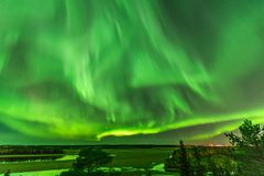 View from scandinavian hill to bright green aurora lights almost on the whole sky over tree tops in Sweden, river, clear skies