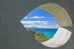 View on scenic beautiful atlantic coastline mountain jaizkibel through eye shape hole in the wall. France Royalty Free Stock Image