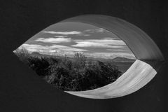 View on scenic beautiful atlantic coastline mountain jaizkibel and trois couronnes through eye shape hole in the wall in black and. View on scenic beautiful Stock Photography