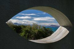 View on scenic beautiful atlantic coastline mountain jaizkibel and trois couronnes through eye shape hole in the wall. France Stock Images