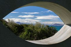 View on scenic beautiful atlantic coastline mountain jaizkibel and trois couronnes through eye shape hole in the wall. France Stock Photo