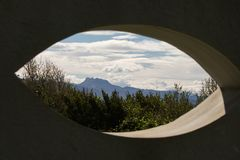 View on scenic beautiful atlantic coastline mountain trois couronnes through eye shape hole in the wall. Creative design Royalty Free Stock Images