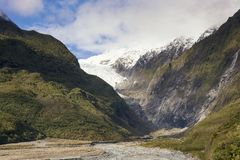 View on the scenic panorama of the Franz Josef Glacier on the west coast of New Zealand. Ice, rocks, valley, beautiful sky, trees and bare ground are all royalty free stock photos