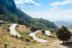 View of the scenic route of the Sierra of Tramontana, Mallorca. View of two cyclists on route on the mountain road with a many curves Stock Photos