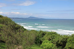 View on scenic seascape from ledge on waves atlantic ocean with mountain jaizkibel in blue sky and clouds, bidart, basuqe country,. Trip to scenic seascape from Royalty Free Stock Photos