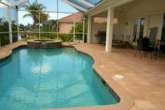 View of screened in swimming pool. Wide angle view of screened in pool and lanai in florida with sitting area Royalty Free Stock Photo