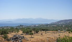 Coast from the top of a hill in Crete. View from scrubland through olive trees down to the Mediterranean Sea. Rocks are in the foreground with hills in the far Royalty Free Stock Photo