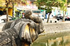 View on a sculpture of elephant near to channel and road. Chiang Mai, Thailand stock images