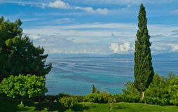 View of sea from Agios Georgios. View out to sea from Agios Georgios, Corfu with cypress trees in foreground Royalty Free Stock Photography