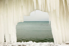 View of the sea through an arch from icicles on a moody day Royalty Free Stock Photography