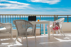 View of the sea from balcony with white table and cheas, blue sk. View of the sea from balcony with white table and cheas Royalty Free Stock Photo