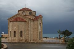 A view of the sea and church before the storm with dark blue clouds approaching the island stock photo