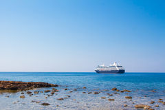 View of the sea coast with stones and boat in Chania, Crete island, Greece. royalty free stock images