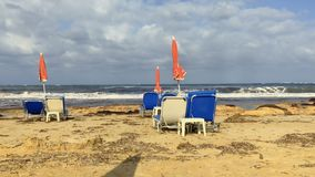 View on the sea with deck chairs and closing umbrellas at the beach. View of beautiful emerald sea with blue cloudy sky. Waves covers the beach. Silence and stock footage