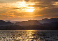 View from the sea on the distant shore  with the setting sun ove Royalty Free Stock Image