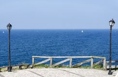 View of the sea with a fence and two lampposts Royalty Free Stock Photo