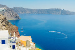 View of the sea with the high coast of the island of Santorini. View of the blue sea and the white yachts with the high coast of the island of Santorini, Greece royalty free stock image
