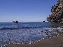 View on sea horizon with old Sailing ship from black sand beach. Playa De Masca with big  cliffs and blue sky background Stock Image