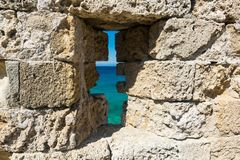 View of the sea through the loophole of the castle wall. View of the sea through the loophole of the ancient castle wall stock image
