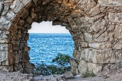 View of the sea through the loophole of the fortress. View of the sea, through the loophole of an ancient fortress Royalty Free Stock Photo
