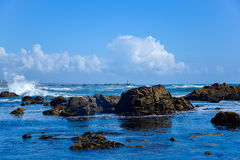 View of sea/ocean with rocks and blue sky Royalty Free Stock Image