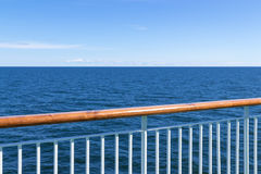 View at the sea from passenger ship. Passenger ship railing with sea and blue sky in the background royalty free stock photo