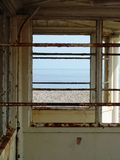 View of the sea through a rusty abandoned beach shelter. A view of the sea and pebbled beach through the window of a rusty, abandoned, metal beach shelter Stock Image