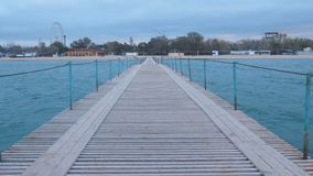 View from the sea pier to the coastal town and sandy beach in evening. stock footage