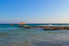 View of the sea. Rocky shallows and a pleasure boat. Cyprus.  Stock Images