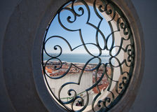 A view of the sea through a round hole in the wall. Figured grid in the window. View of Lisbon Royalty Free Stock Photo