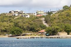 View of Beach, Boats, Jetty and Houses; Saline Bay, Mayreau Island, Saint Vincent and the Grenadines, Eastern Caribbean. View from the sea of Saline Bay with Stock Images