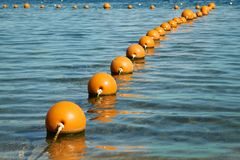 View of the sea from a shore with a long line of orange colored marker buoys floating royalty free stock images