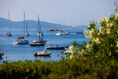 View of the sea and of the small port with motor boats and sailing boats Stock Image