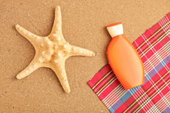 A view of a sea star and sun cream on a beach Stock Images