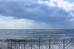 View of the sea before the storm. Sudak. Crimea. The sea behind a fence, storm clouds in the sky Royalty Free Stock Photos