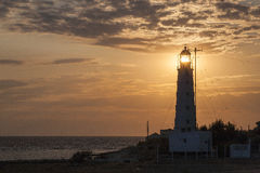 View at the sea with sun lighting through lamp of lighthouse Royalty Free Stock Photos