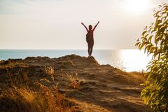 Tourist with backpack standing on sea coast with raised hands. stock images