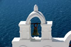 View of sea surface through traditional Greek white church arch with cross and bells in Oia village of Cyclades Island. Santorini, Greece Stock Photo