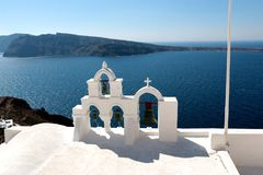 View of sea surface through traditional Greek white church arch with cross and bells in Oia village of Cyclades Island, Santorini, Royalty Free Stock Photo